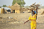 A woman living in the Aradib Camp for internally displaced persons outside the village of Goz Amer, Chad, carries firewood home to her family's hut. Some 28,000 people live in precarious conditions in this camp. More than 180,000 residents of eastern Chad have been displaced by violence spilling over from neighboring Darfur, inter-ethnic conflict, and fighting between rebels and the Chadian government. Women who gather firewood are frequent targets for assault and rape by militias that lurk outside the camps.