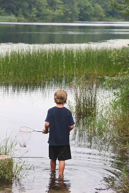 Young boy wading into water carrying a net.