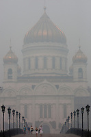 Moscow, Russia, 08/08/2010. .People wear protective masks as they cross a bridge by the Cathedral of Christ the Saviour in the worst smog so far in the record high temperatures of the continuing heatwave. Peat and forest fires in the countryside surrounding Moscow have resulted in the Russian capital being blanketed in heavy smog.