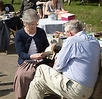 Elderly couple browsing books at village fete event, Suffolk, England