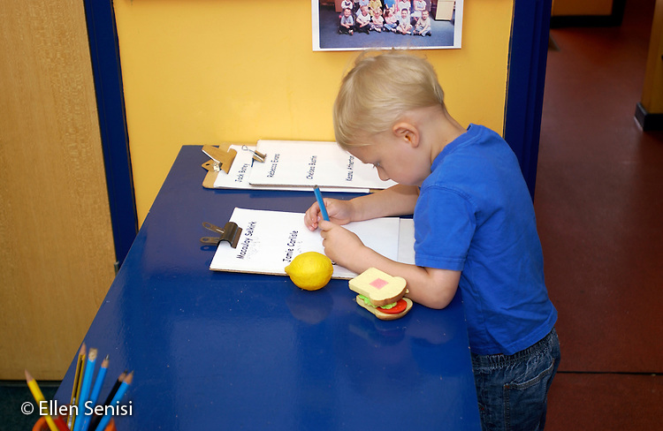MR / Abingdon, Oxfordshire, England.Thomas Reade Primary School.Foundation Class for ages 3-5 .Boy signs in on clipboard at beginning of school day.  Daily name recognition and writing reinforces this basic skill..(Ages 3-4 attend this class half-day, age 5 attends full-day).©Ellen B. Senisi