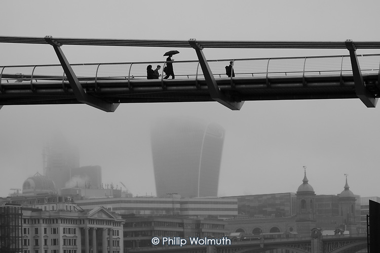 Man with an umbrella crosses the Thames Millenium Bridge in heavy mist.