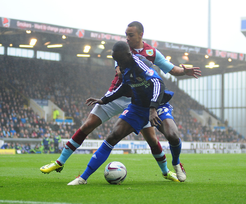 Middlesbrough's Albert Adomah shields the ball from Burnley's Junior Stanislas <br /> <br /> Photo by Chris Vaughan/CameraSport<br /> <br /> Football - The Football League Sky Bet Championship - Burnley v Middlesbrough - Saturday 12th April 2014 - Turf Moor - Burnley<br /> <br /> &copy; CameraSport - 43 Linden Ave. Countesthorpe. Leicester. England. LE8 5PG - Tel: +44 (0) 116 277 4147 - admin@camerasport.com - www.camerasport.com