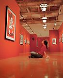 USA, California, Santa Monica, a young woman sits and admires artwork at an exhibit at the Santa Monica Public Library