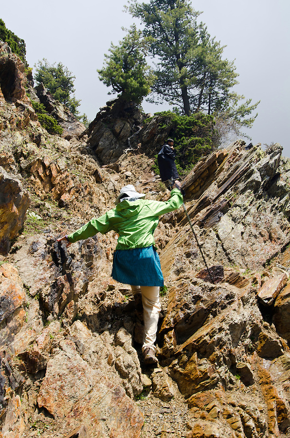 Female trekker scrambling up a rocky section of trail, Western Himalayan Mountains, Kashmir, India..