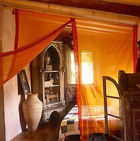 A rustic bedroom with an orange sheer curtain turned back to reveal a display cabinet in the corner.
