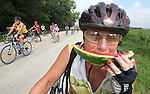 Diane Potter of Cedar Rapids savors a cold slice of watermelon near the top of Potter Hill outside of Graf on Saturday.  Many riders said the mile long, steep hill was the hardest hill they've ever had to climb.  Many did not make it up without stopping to walk their bikes.