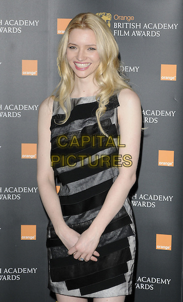 TALULAH RILEY  .The nominations for The Orange British Academy Film Awards (BAFTAs) at BAFTA headquarters, London, England..January 18th, 2011.half length black grey gray dress sleeveless smiling.CAP/CAN.©Can Nguyen/Capital Pictures.