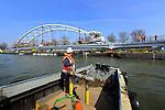 NIEUWEGEIN - Langs het Amsterdam-Rijnkanaal monteren medewerkers van bouwcombinatie KWS - Mercon de boog op het wegdek van de nieuwe Overeindsebrug. De stalen brug is de afgelopen dagen vanaf de werf van Mercon in Gorinchem per ponton vervoerd naar Nieuwegein en wordt dit weekend in opdracht van Rijkswaterstaat met hulp van drijvende kranen gewisseld met de oude brug. De renovatie van de Overeindsebrug is onderdeel van het project KARGO (Kunstwerken Amsterdam-Rijnkanaal Groot Onderhoud) waarbij Rijkswaterstaat acht stalen bruggen vernieuwd. COPYRIGHT TON BORSBOOM