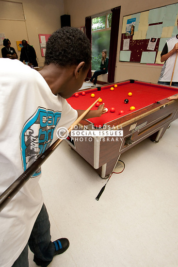 Teenage boy playing pool during break in summer class Haringey London UK