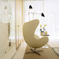 A pair of black angle-poise lamps stand over a white leather Egg chair by Arne Jacobsen