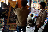 People look at thangka, a traditional Tibetan Buddhist painting, in an artists' studio outside the Labrang Monastery in Xiahe, Gansu, China. Xiahe, home of the Labrang Monastery, is an important site for Tibetan Buddhists.  The population of the town is divided between ethnic Tibetans, Muslims, and Han Chinese.