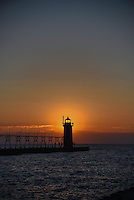 Sunset glowing behind the South Haven lighthouse with rich horizontal striped colors on the horizon.