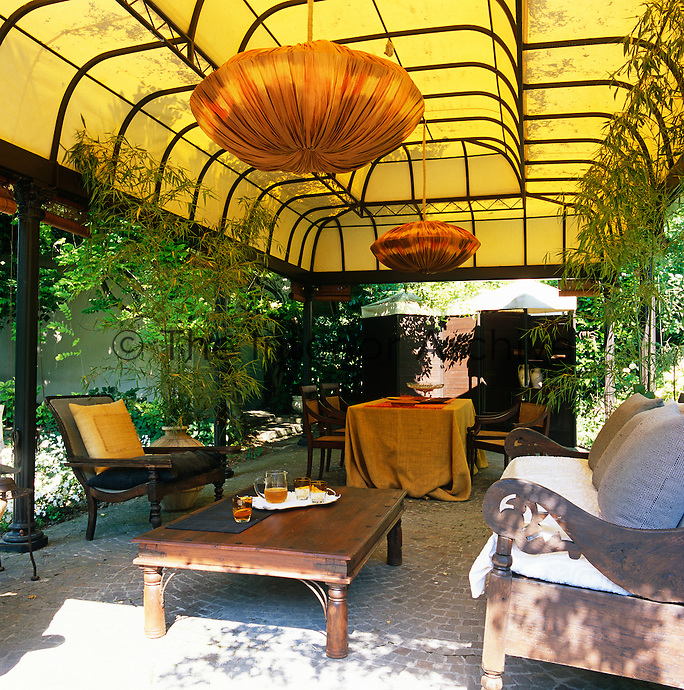 One of three outdoor dining areas, this one has a permanent gazebo-style roof and a pair of fabric-clad chandeliers