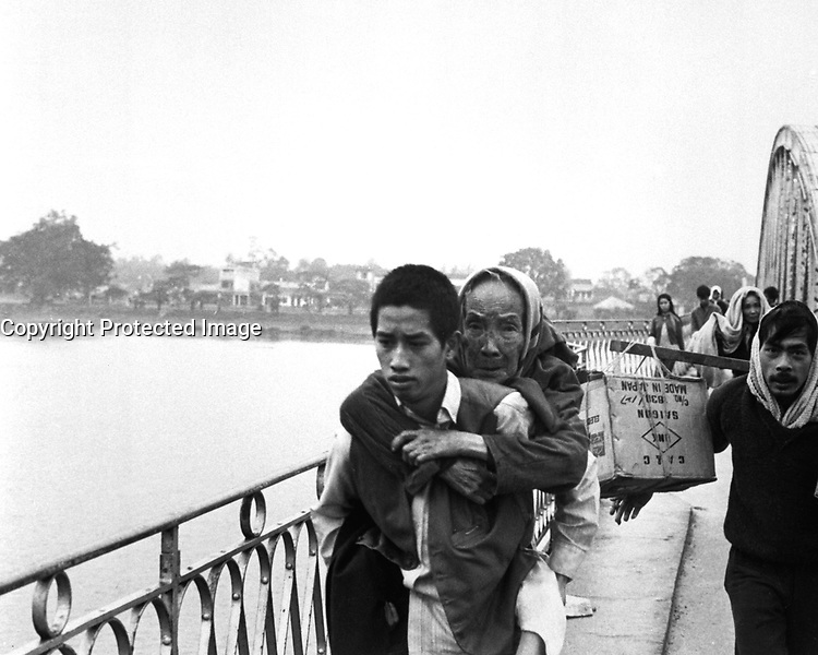 This bridge over the Perfume River in Hue was still standing as these refugees fled across it to escape Tet fighting, but it soon was dropped into the river by the communists.  1968. (USIA)<br /> EXACT DATE SHOT UNKNOWN<br /> NARA FILE #:  306-MVP-22-6<br /> WAR & CONFLICT BOOK #:  405