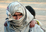 An Afghan refugee woman and child await transfer from Jalozai refugee camp to a new camp near the Afghan border.