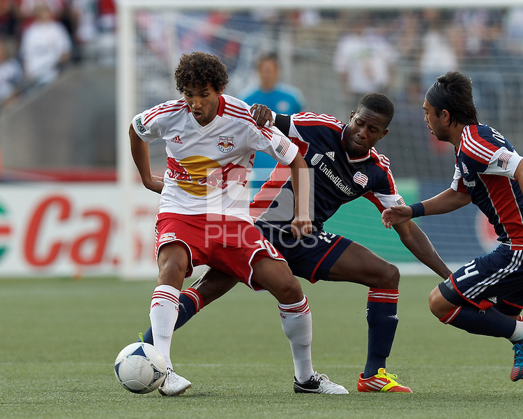 New York Red Bulls midfielder Mehdi Ballouchy (10) controls the ball as New England Revolution midfielder Clyde Simms (19) pressures and New England Revolution midfielder Lee Nguyen (24) closes. In a Major League Soccer (MLS) match, New England Revolution defeated New York Red Bulls, 2-0, at Gillette Stadium on July 8, 2012.