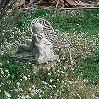 A detail of a garden with a wicker chair beside a statue of a boy, set amongst a mass of white flowers.
