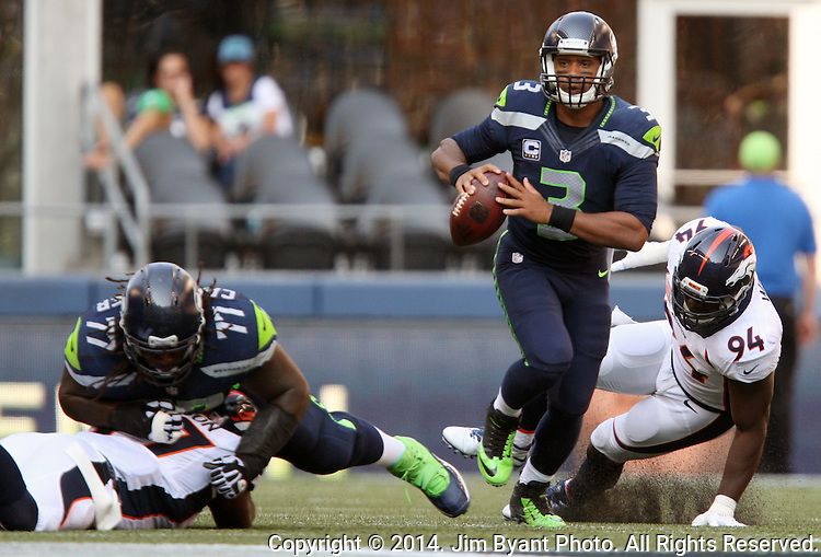 Seattle Seahawks quarterback Russell Wilson (3) looks to pass as he scrambles away from Denver Broncos defensive end DeMarcusWare (94) ) at CenturyLink Field in Seattle, Washington on September 21, 2014.  Wilson completed 24 of 34 passes for 258 yards, two touchdowns and one interception in the 26-20 overtime win against the Broncos.  ©2014. Jim Bryant Photo. All rights Reserved.