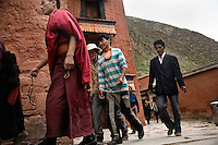 Tibetan Pilgrims and monks circle a temple at the Labrang Monastery in Xiahe, Gansu, China. Xiahe, home of the Labrang Monastery, is an important site for Tibetan Buddhists.  The population of the town is divided between ethnic Tibetans, Muslims, and Han Chinese.