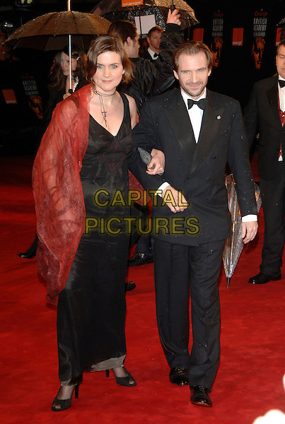 SOPHIE FIENNES & RALPH FIENNES.Arrivals at The Orange British Academy Film Awards .BAFTA's at the Odeon Leicester Square, London, England.February 19th, 2006.Ref: PL.bafta baftas full length black dress tuxedo arms linked red sheer.www.capitalpictures.com.sales@capitalpictures.com.© Capital Pictures.