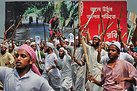 A group of protesters armed with bamboo sticks in front of a billboard of a modern Bangladeshi woman, illustrates Bangladesh in the twenty-first century, during a demonstration against women's rights legislation in Narayangang, near Dhaka, Bangladesh.