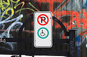 Handicap parking only zone,  graffiti painted wall in background
