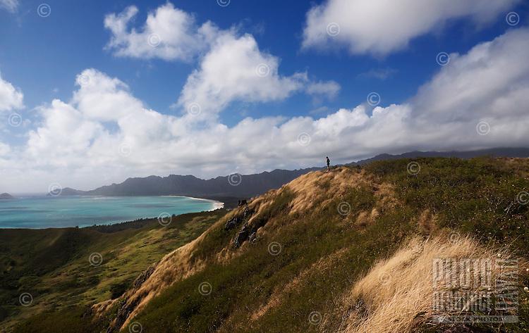 At sunrise, a woman looks out at the ocean at Lanikai, Windward O'ahu.