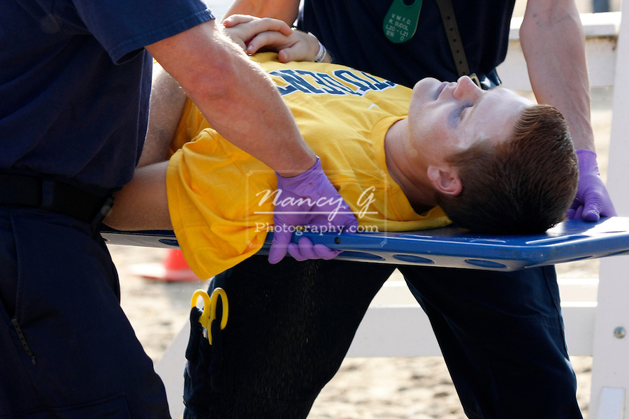 Two EMTs carrying a victim on a backboard off a beach