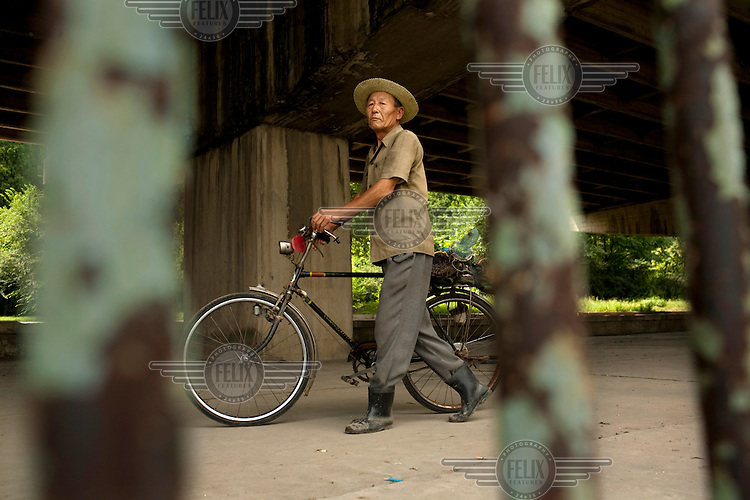 A man pushes his bicycle along a river bank in Pyongyang.