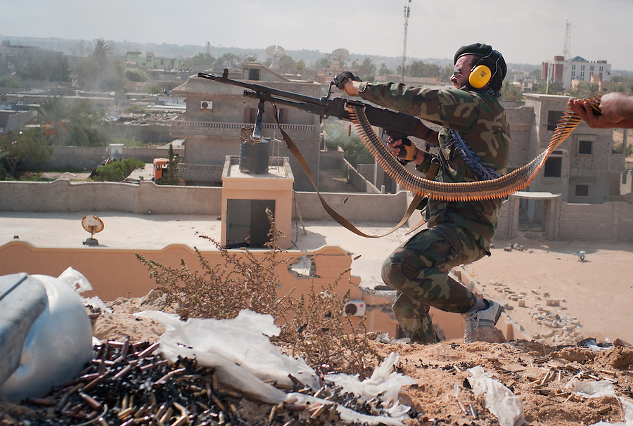 Anti-Gaddafi fighter fires belt-fed machine gun towards Gaddafi loyalist position in Sirte, Libya.