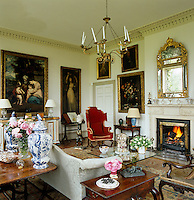 A Regency mirror hangs above the fireplace in the drawing room which is filled with artwork