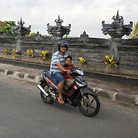 Bali, Indonesia.  Road safety.  Father and Son on Motorbike, no helmet on Boy.