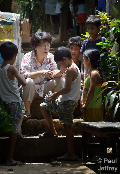 The Rev. Grace Choi is a United Methodist missionary serving in the Philippines, where she is community health worker in the outreach programs of Harris Memorial College. A native of Korea, she also teaches piano and voice at the music department of the school. Here she visits with children in the Upper Javier neighborhood of the town of Taytay, where she carries out health work. .