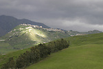 Sunlight on hill with dark clouds all around Sicilian mountain town.