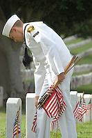 Saturday, May 22, 2009.  Fort Rosecrans National Cemetery, San Diego California, USA:  Cadet George Mick (15) of the Miramar based United States Naval Cadet Corps places a flag at grave sites in the Fort Rosecrans National Cemetery.  Hundreds of boy scouts, girl scouts and their parents fanned out across the cemetery to plant flags at each grave site to mark Memorial Day..