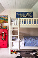 White painted bunk beds save space in the children's bedroom. The wallpaper is Spot & Star in pink by Molly Mahon.
