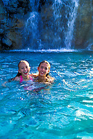 Two girls playing in a pool with waterfall behind