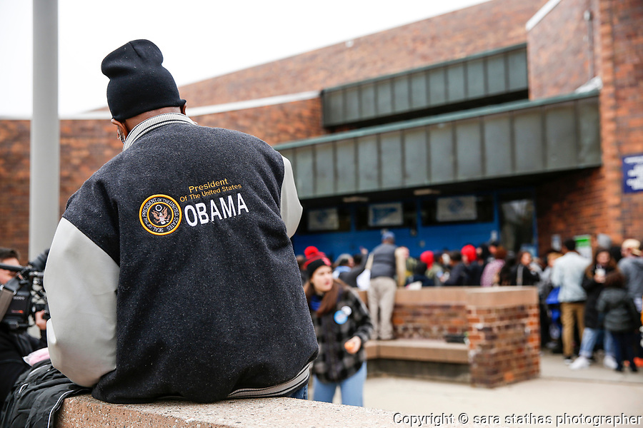 "A man sits on a stoop wearing an ""Obama"" jacket outside of a venue that former president Barack Obama is speaking at in Milwaukee, Wisconsin."