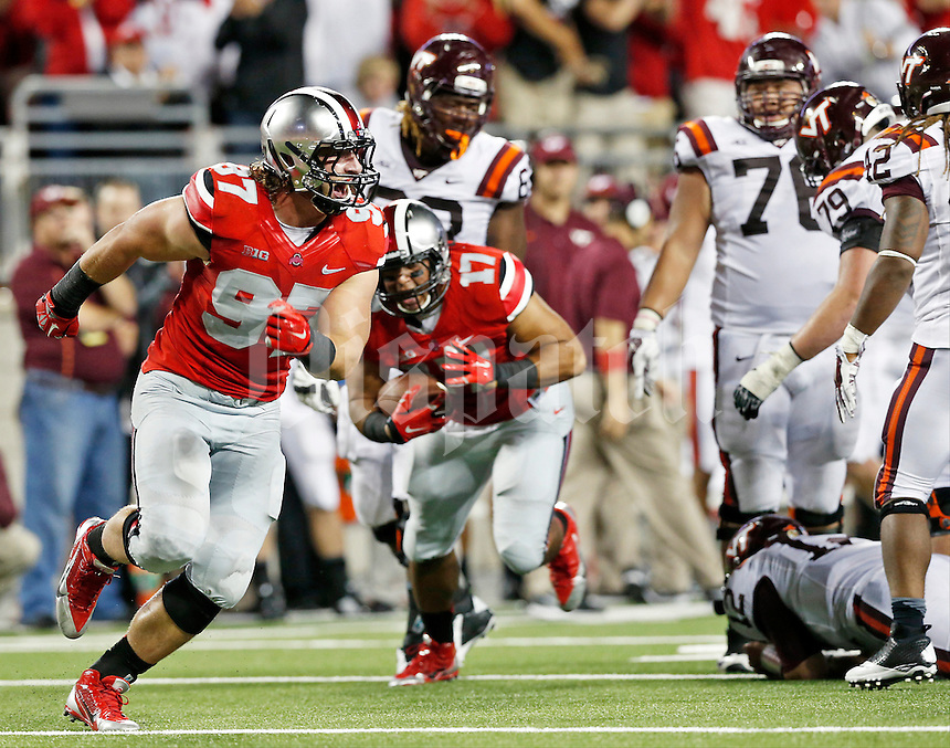 Ohio State Buckeyes defensive lineman Joey Bosa (97) celebrates after tackling Virginia Tech Hokies quarterback Michael Brewer (12) and causing a fumble recovered by Ohio State Buckeyes defensive lineman Rashad Frazier (17) during Saturday's NCAA Division I football game at Ohio Stadium in Columbus on September 6, 2014. Virginia Tech won the game 35-21. (Dispatch Photo by Barbara J. Perenic)