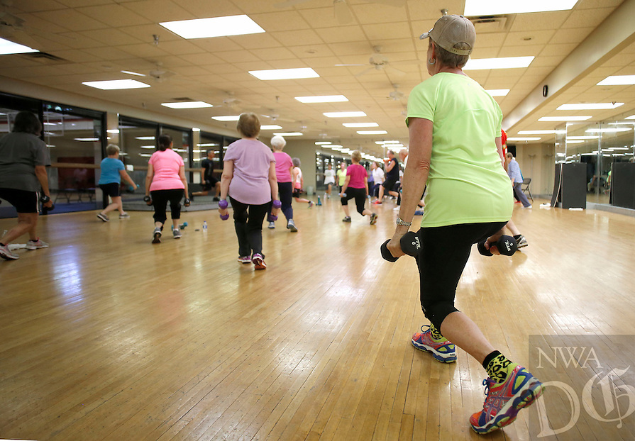 NWA Democrat-Gazette/DAVID GOTTSCHALK - Beverly Loomis (right) participates in the Young at Heart fitness class at the Fayetteville Athletic Club Monday, July13 , 2015 under the direction of personal trainer Reuben Reina.