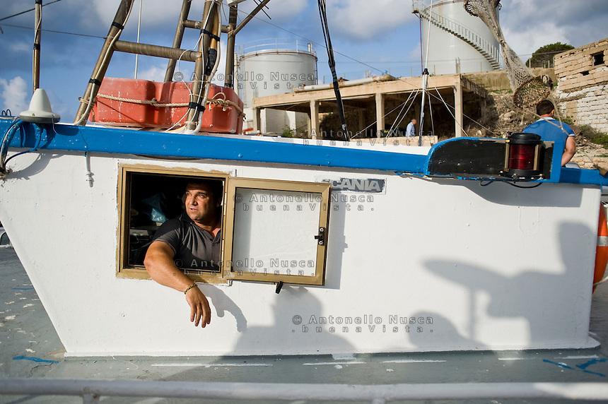 Un pescatore parla ai giornalisti nel porto dell'isola di Lampedusa.