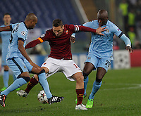 AS Roma's Francesco Totti  challanged by Manchester City's Eliaquim Mangala and Manchester City's Martin Demichelis during the Champions League Group E soccer match between As Roma and Manchester City  at the Olympic Stadium in Rome December 10 , 2014.