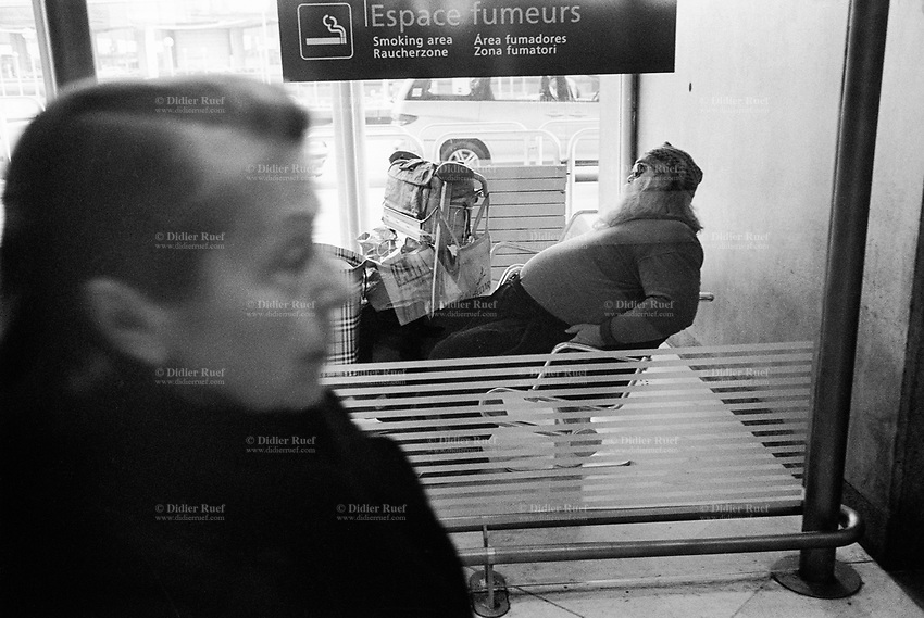 France. Ile-de-france Department. Paris-Charles de Gaulle Airport. A big old fat man with a beard and a hat is seated in a smoking area. A woman passes-by and walks away. Paris-Charles de Gaulle Airport (French: Aéroport Paris-Charles de Gaulle), also known as Roissy Airport (or just Roissy in French), is one the largest airport in France. 25.02.05 © 2005 Didier Ruef