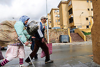 Una donna marocchina, portrice di merci, accanto il suo accompagnatore nei presso dell'ingresso del centro commerciale di Las Naves. Ceuta, 8 febbraio 2010<br /> <br /> A moroccan woman, goods bearer, with her companion near Las Naves shopping mall. Ceuta, February 8, 2010