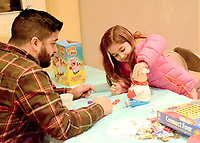 Janelle Jessen/Herald-Leader<br /> Manny Anchondo, left, and his daughter Emma Anchondo played Pop the Pig during Family Game Night on Friday.