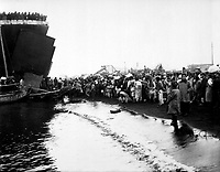 Korean natives prepare to board an LST during the evacuation of Hungnam, while other refugees unload some of their meager belongings from an ox-cart and load them on a fishing boat.  December 19, 1950. (Navy)<br /> NARA FILE #:  080-G-424096<br /> WAR &amp; CONFLICT BOOK #:  1479
