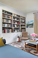 Built-in bookcase and cupboards line one wall of a sitting room