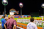 Night baseball game, Brooklyn Cyclones and Tri-City ValleyCats baseball game during National Anthem before start of game at MCU Stadium. Tri-City ValleyCats team seen from back on field while facing American flag in distance (dimly glimpsed at full resolution), with scoreboard, and Coney Island amusement park at side. Fans from back, and glimpse of cheerleaders also seen. 2nd game of double-header.