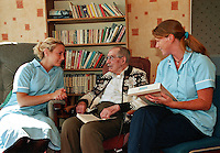 Elderely resident of a care home with his nurses. They are reading a book together.